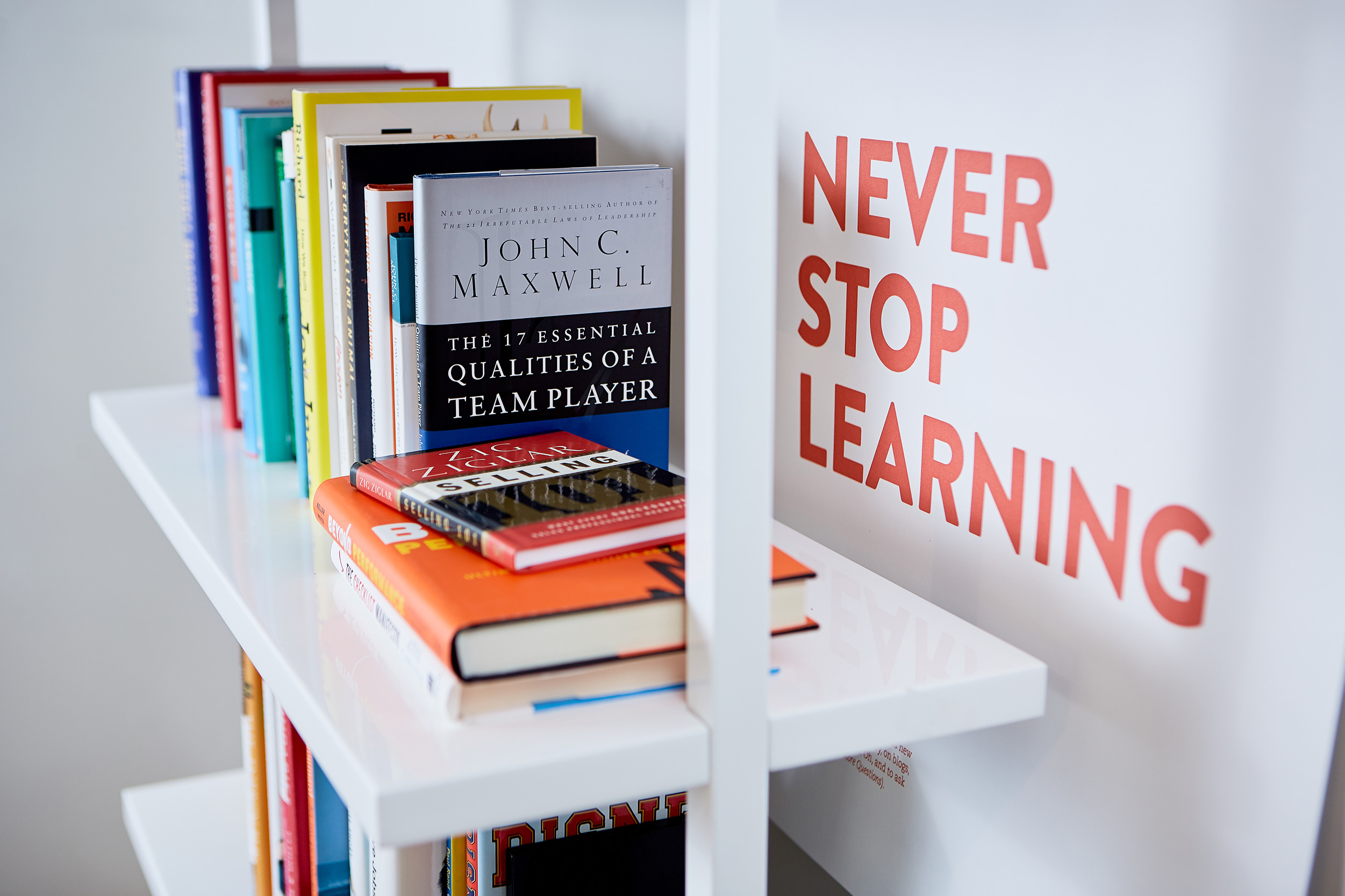 Photo of books on a shelf with a nearby poster that reads Never Stop Learning