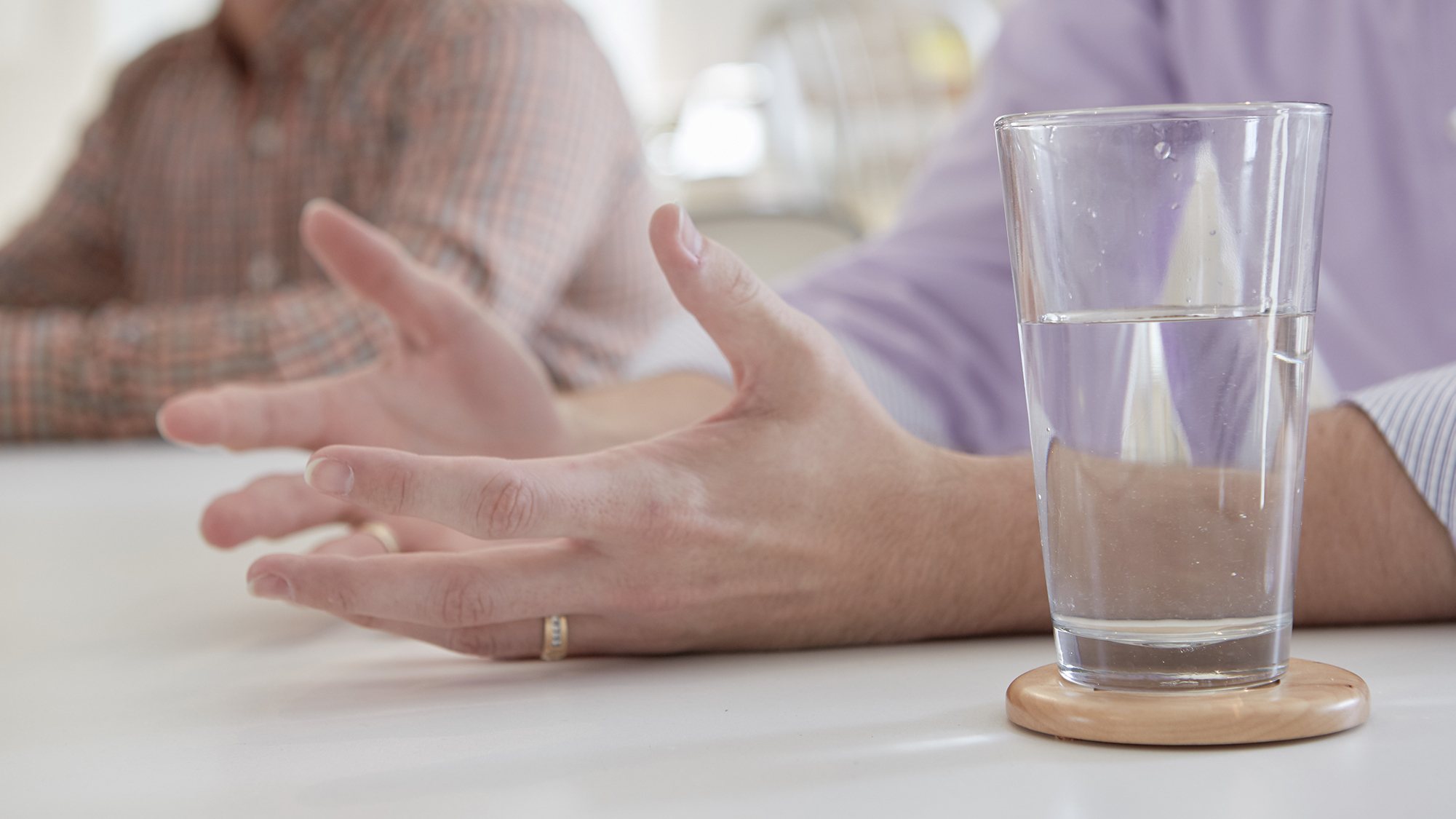 Photo of hands open palm up next to a glass of water.