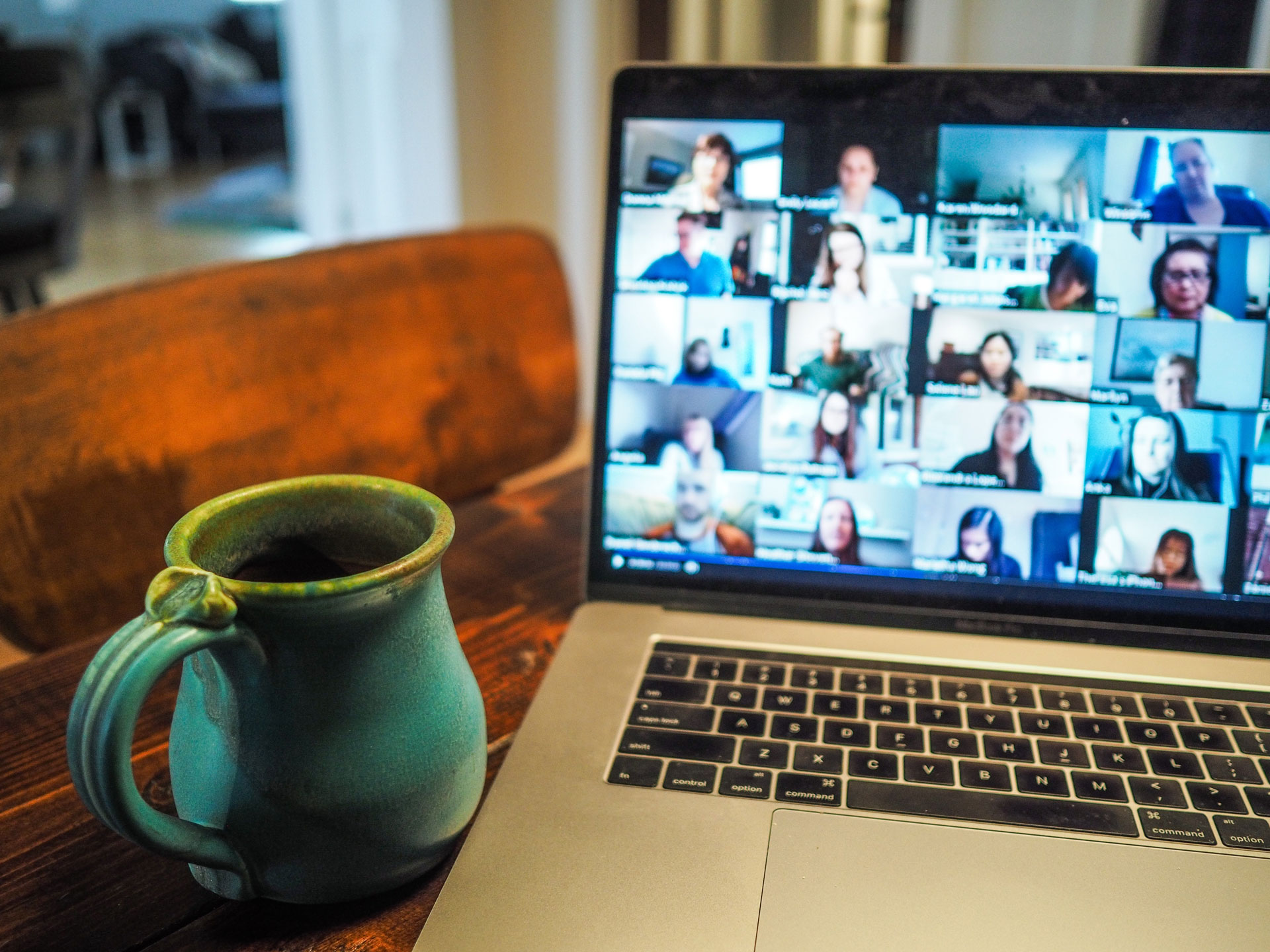 Photo of a laptop during a video conference call showing multiple participants via their webcam videos.